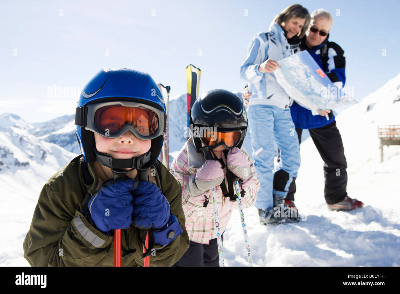 Grandparents reading piste map with kids - Stock Image