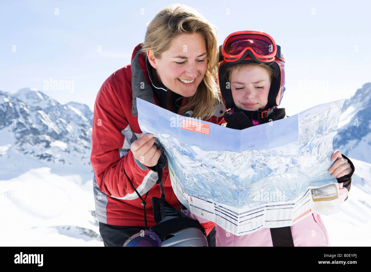 Mother and daughter reading piste map - Stock Image