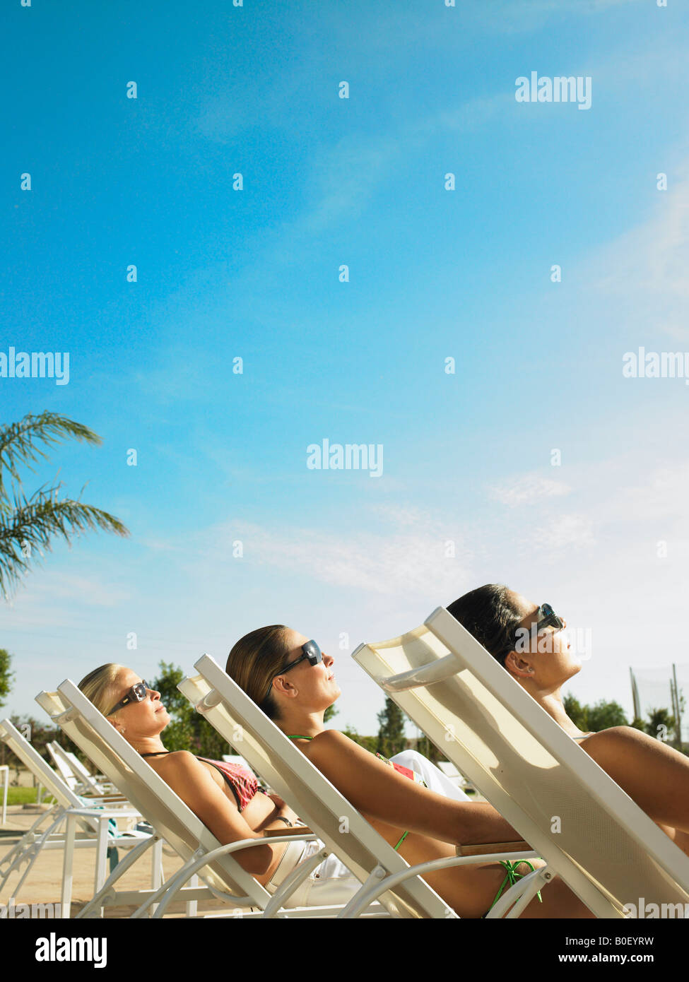 Three ladies relaxing in the sun - Stock Image