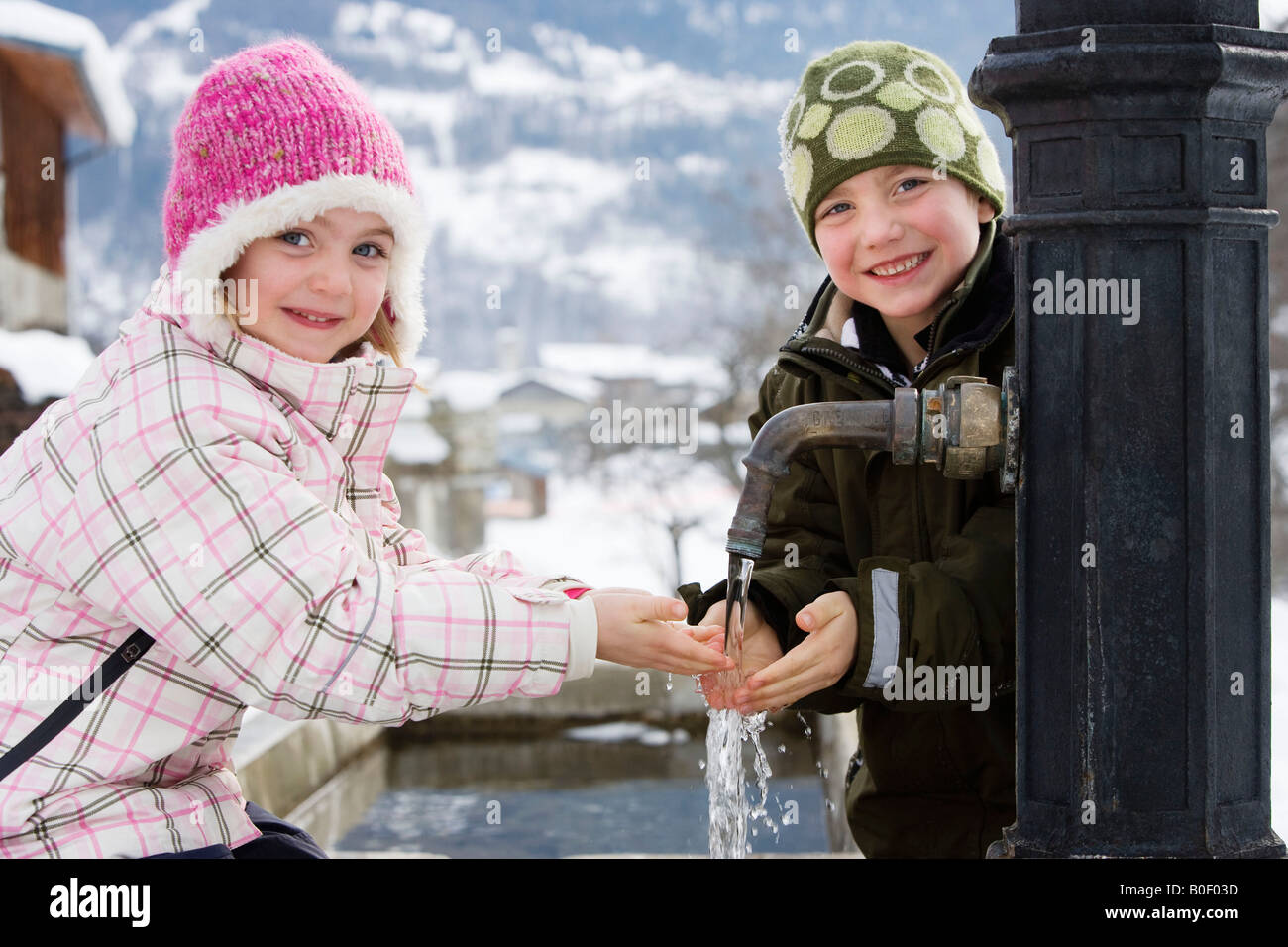 Boy and girl holding hands under tap - Stock Image