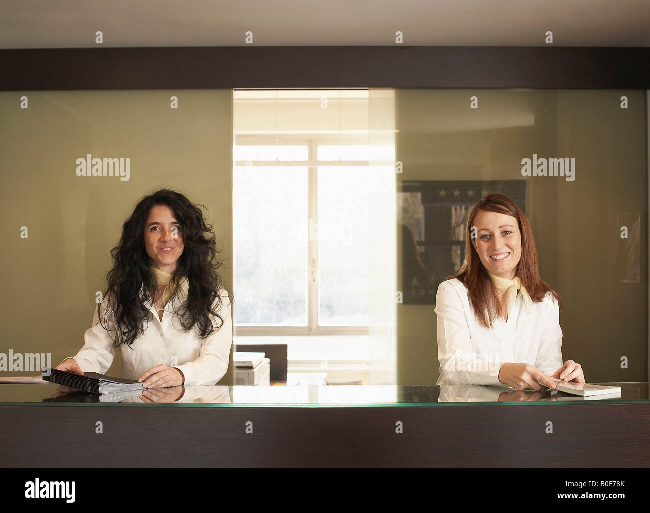 Two Receptionists behind hotel counter - Stock Image