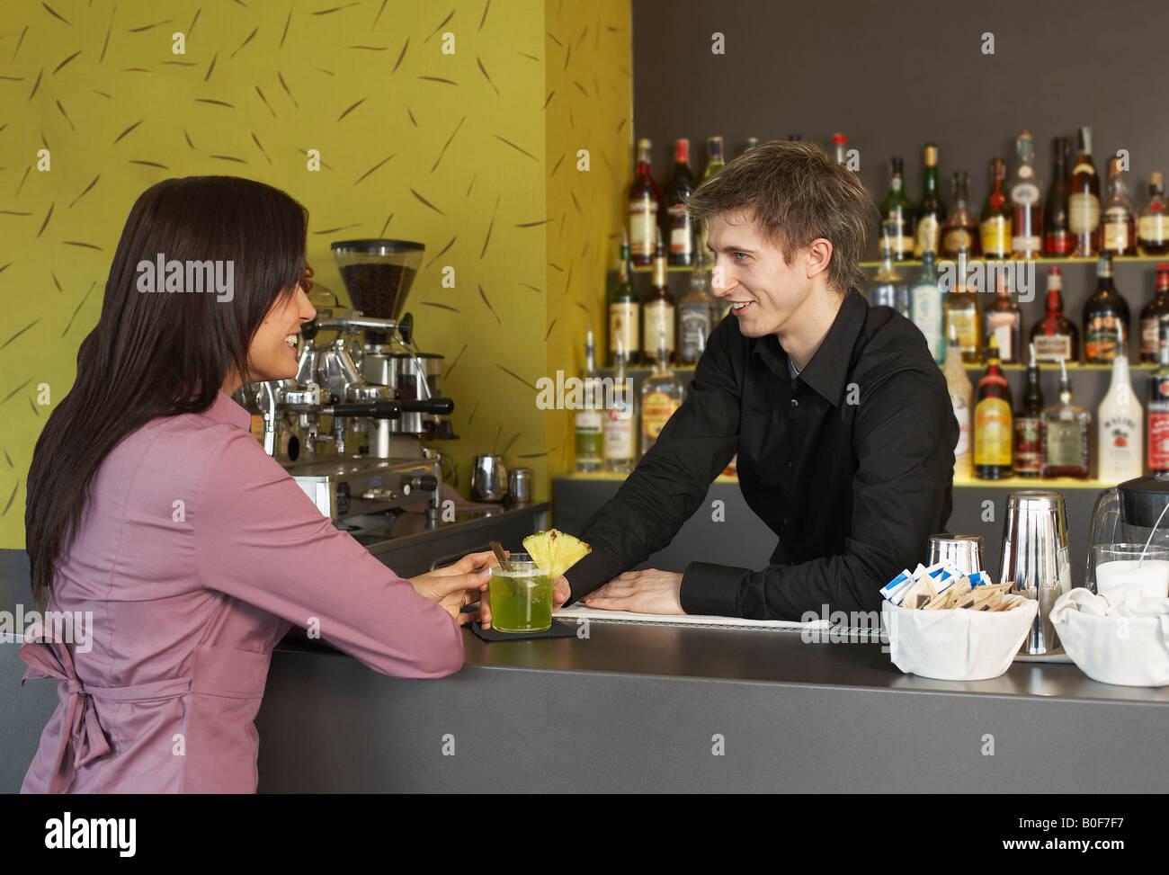 Young woman talking to barman - Stock Image