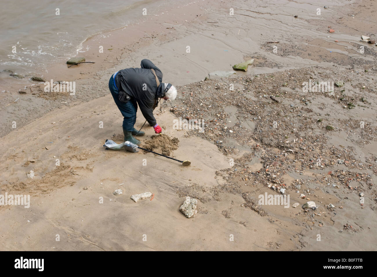 metal Detectorist searches the Foreshore near Greenwich Pier Bends to search a pile of sand in more detail - Stock Image