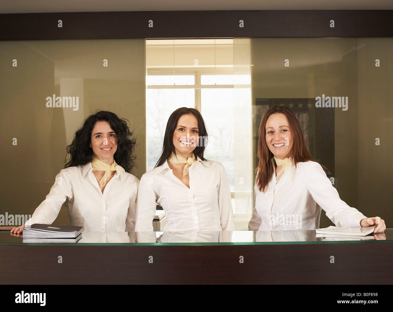 Receptionists behind hotel counter - Stock Image