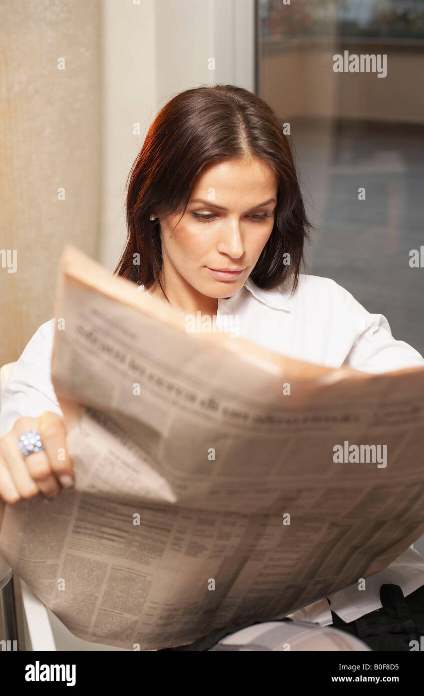 Young woman reading financial newspaper Stock Photo