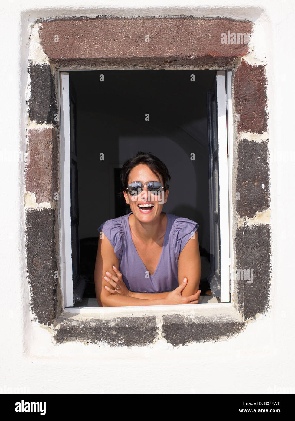 Woman looking through window, smiling Stock Photo
