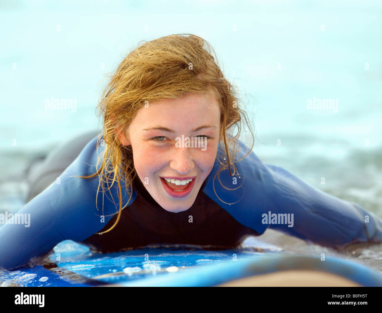 Female on surfboard taking small wave - Stock Image