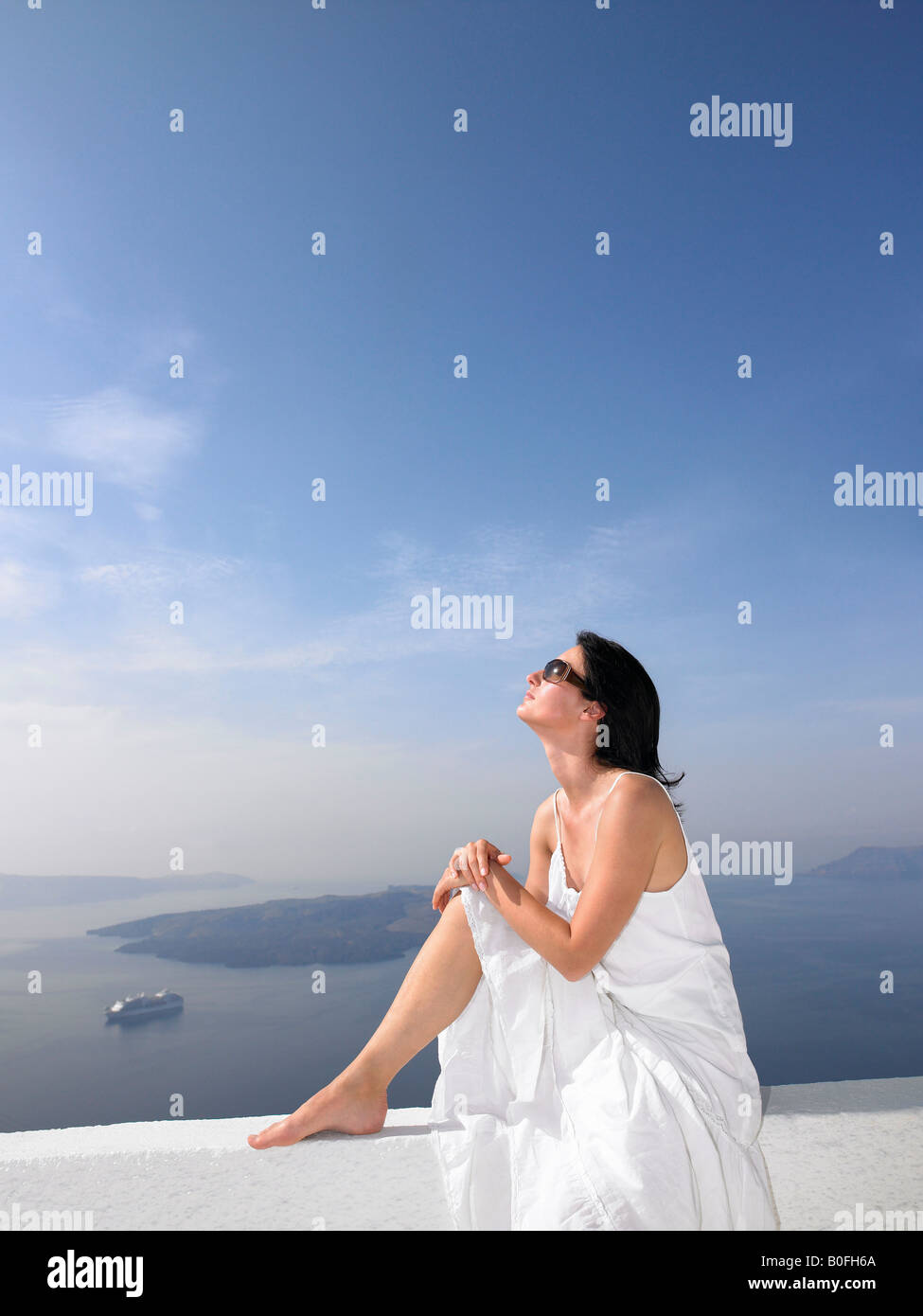 Woman resting on a white wall - Stock Image