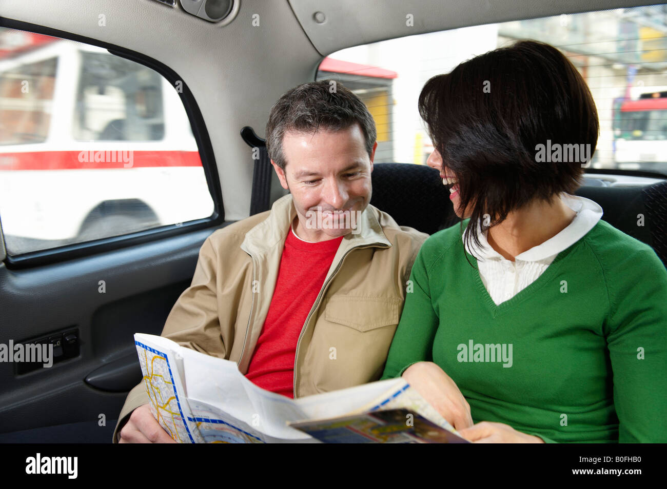 Couple reading map in London Taxi - Stock Image