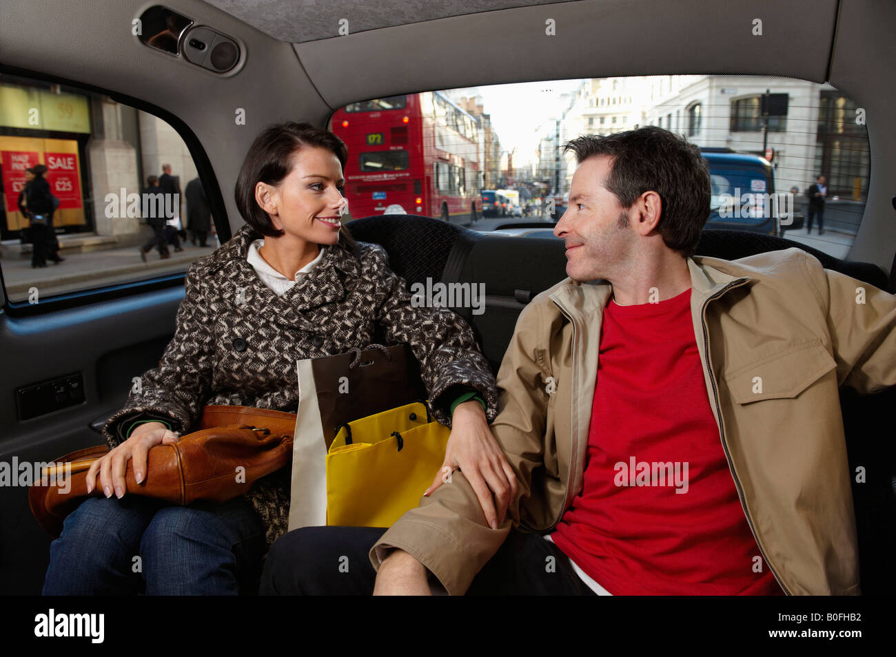 Couple in London taxi with bags - Stock Image