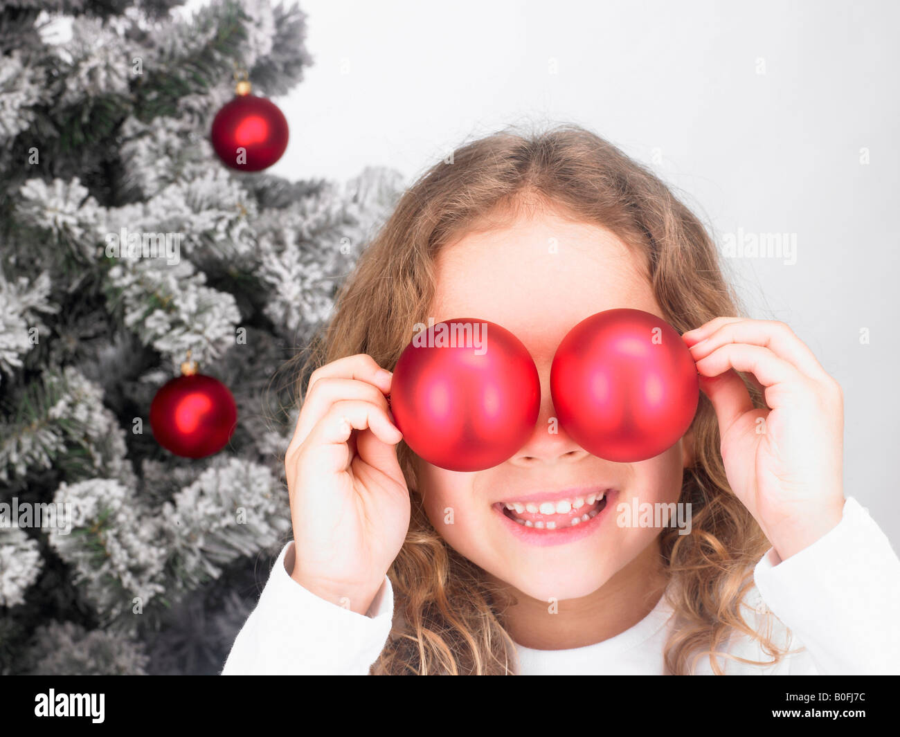 Girl playing with Christmas decoration - Stock Image