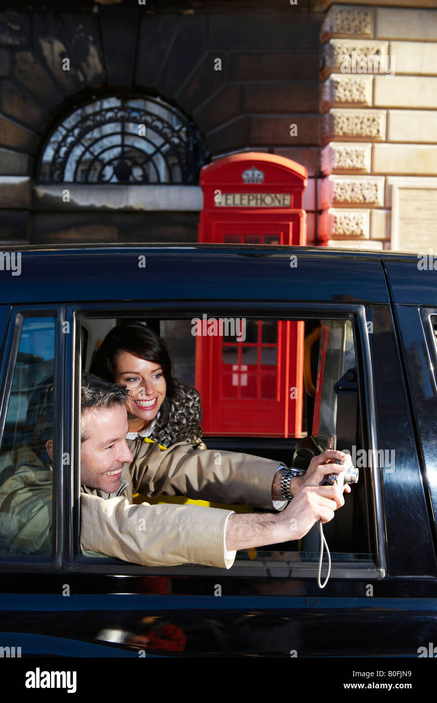 Couple taking snap from taxi window - Stock Image