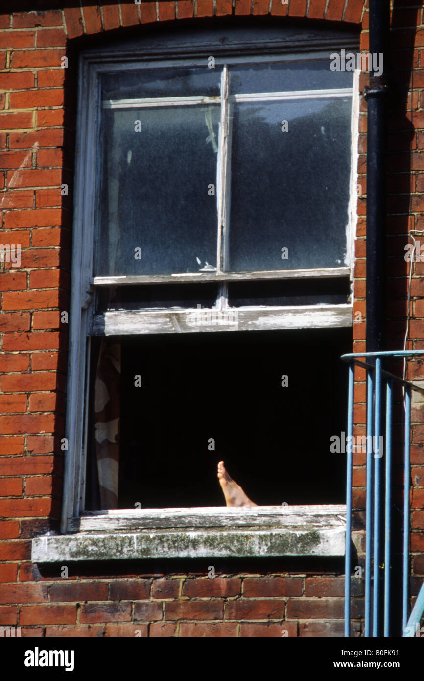 lazy days as a person relaxes in an apartment with a bare foot sticking out of the window portsmouth uk - Stock Image