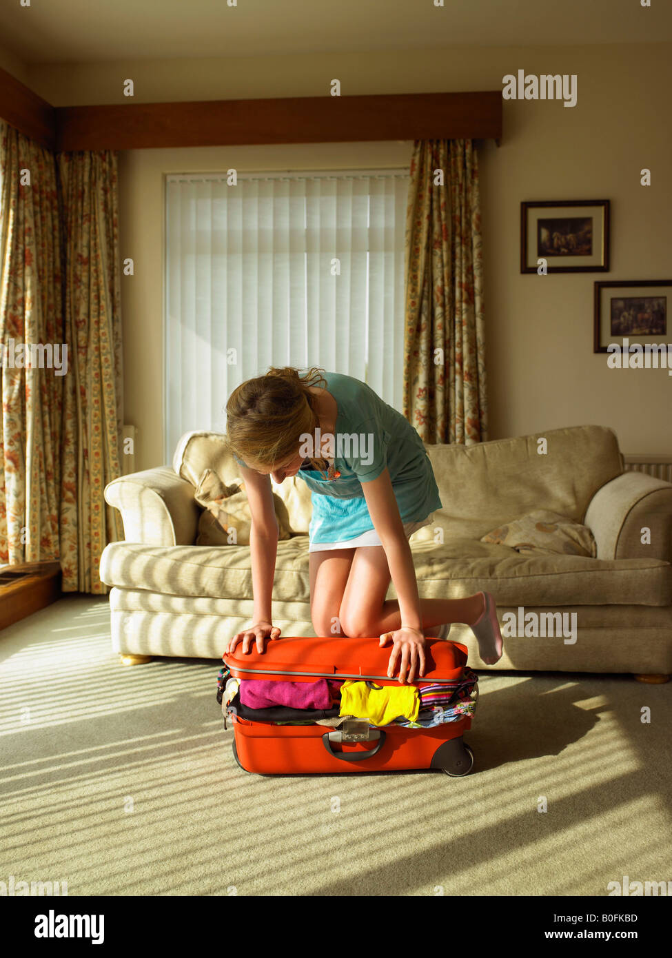 Young female trying to close suitcase - Stock Image