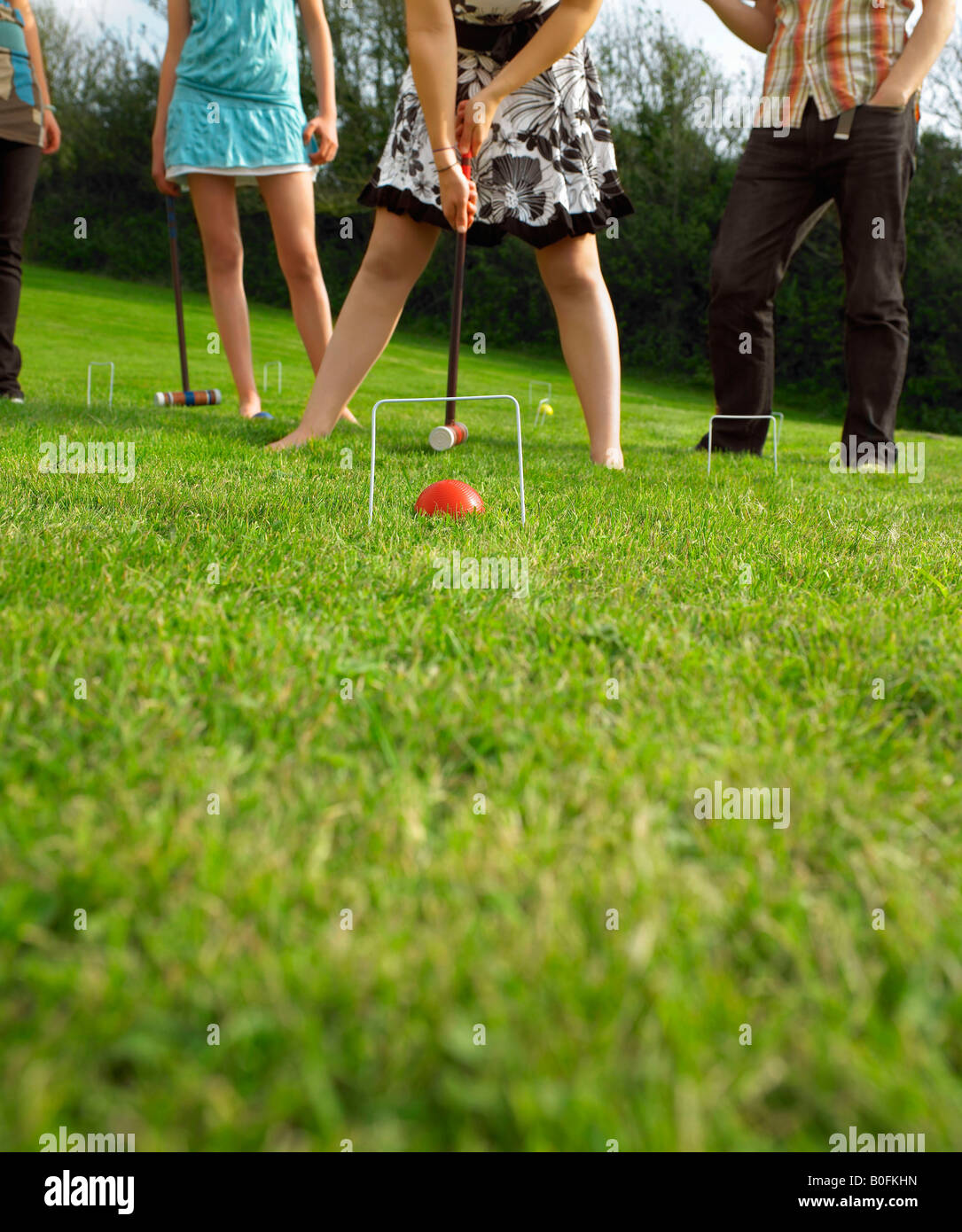 Man and women playing croquet in garden - Stock Image