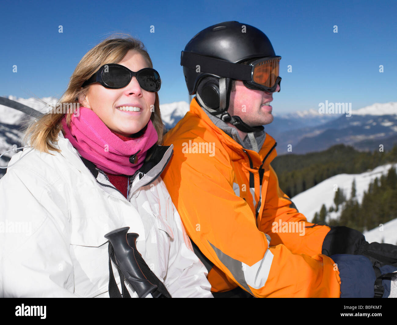 Smiling couple on ski lift - Stock Image
