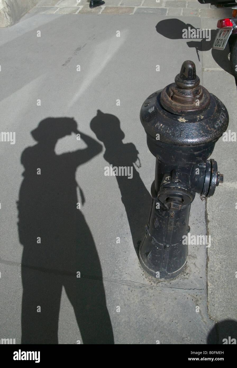 Shadow of tourist take picture with fire hydrant on the sidewalk Vienna Austria - Stock Image