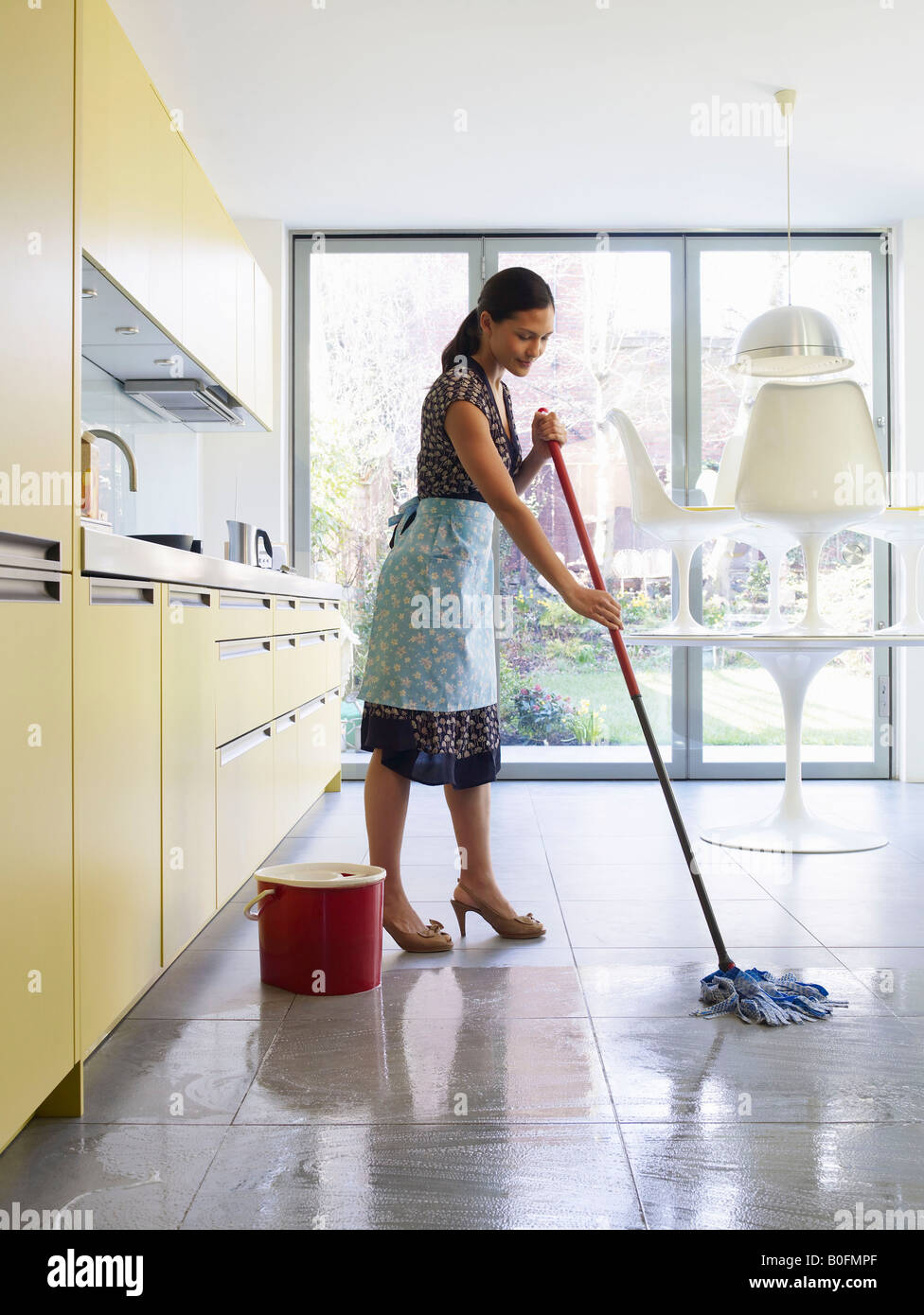 Young woman mopping kitchen floor Stock Photo   Alamy