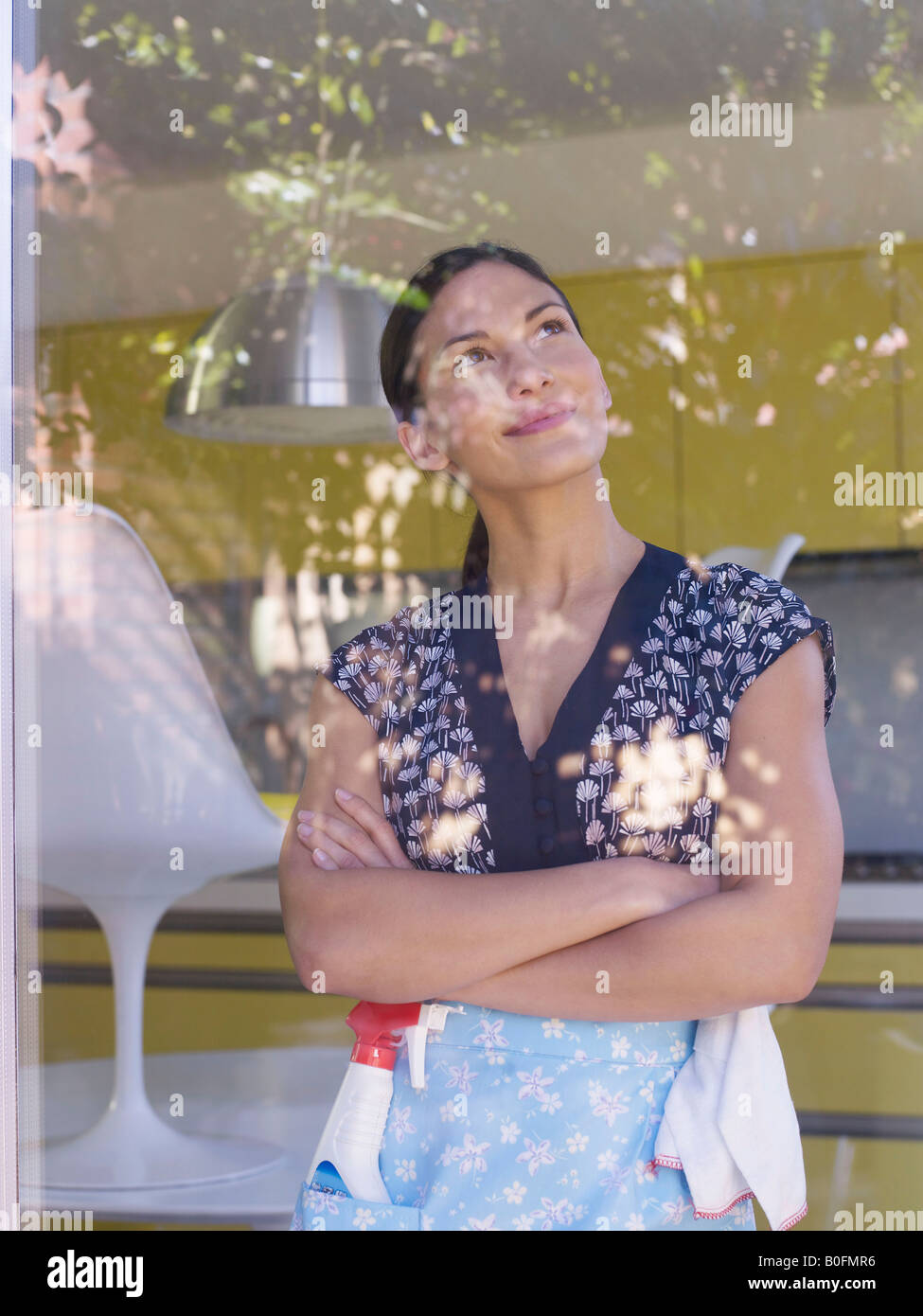 Young woman daydreaming whilst cleaning Stock Photo