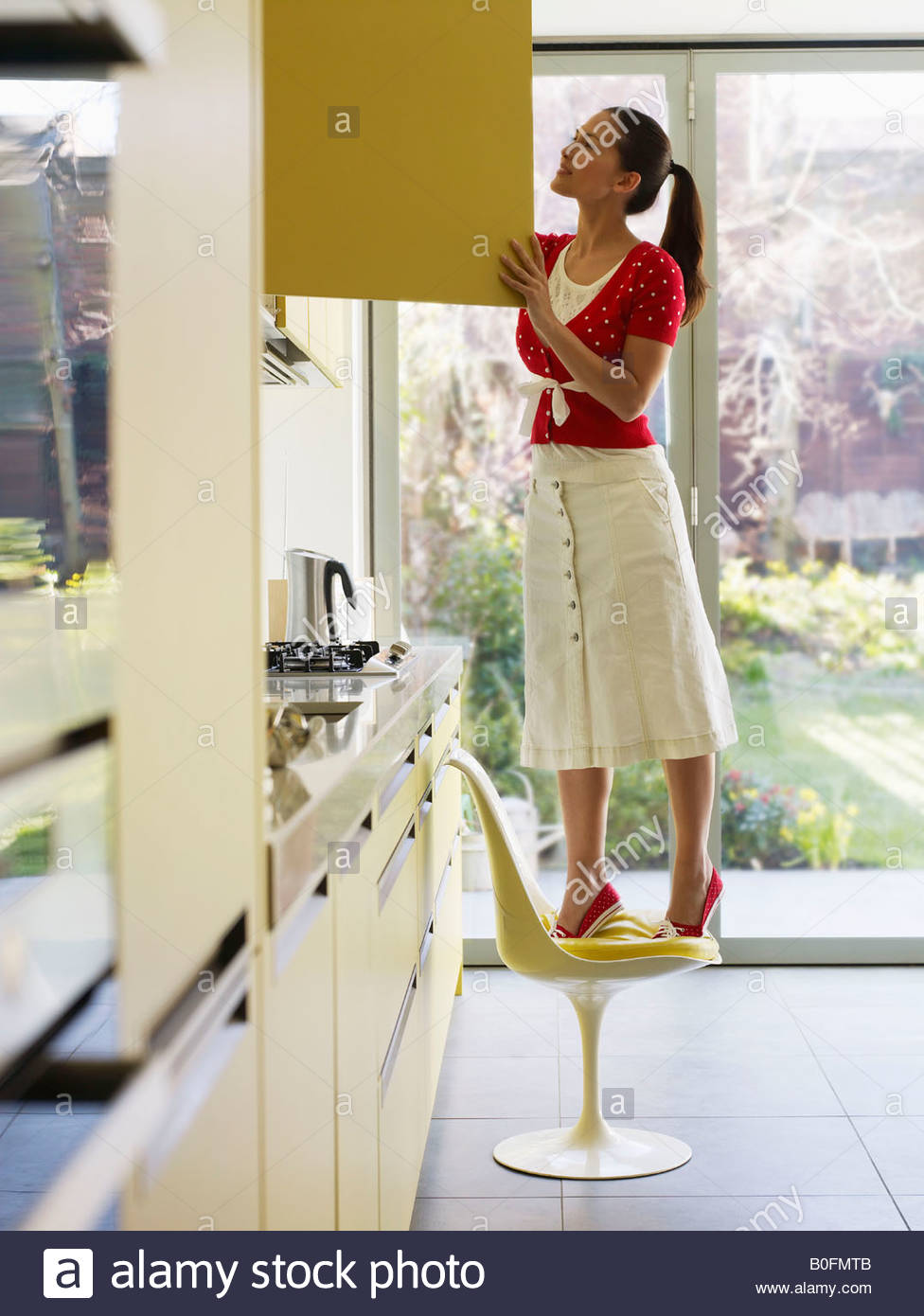 Young woman on chair looking in cupboard - Stock Image