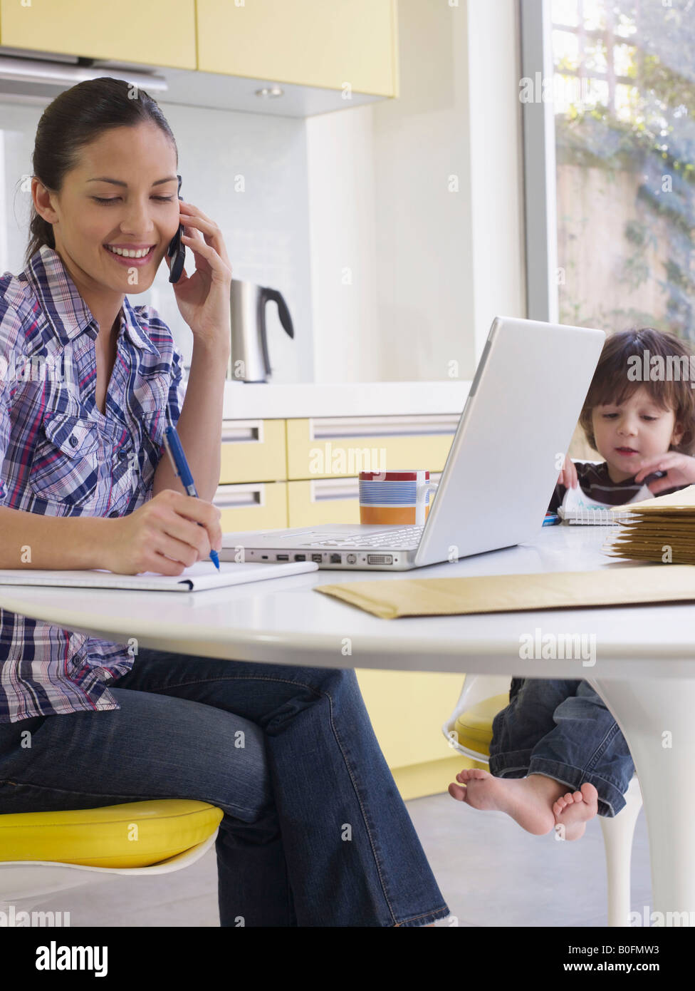 Woman working at home, son at table - Stock Image
