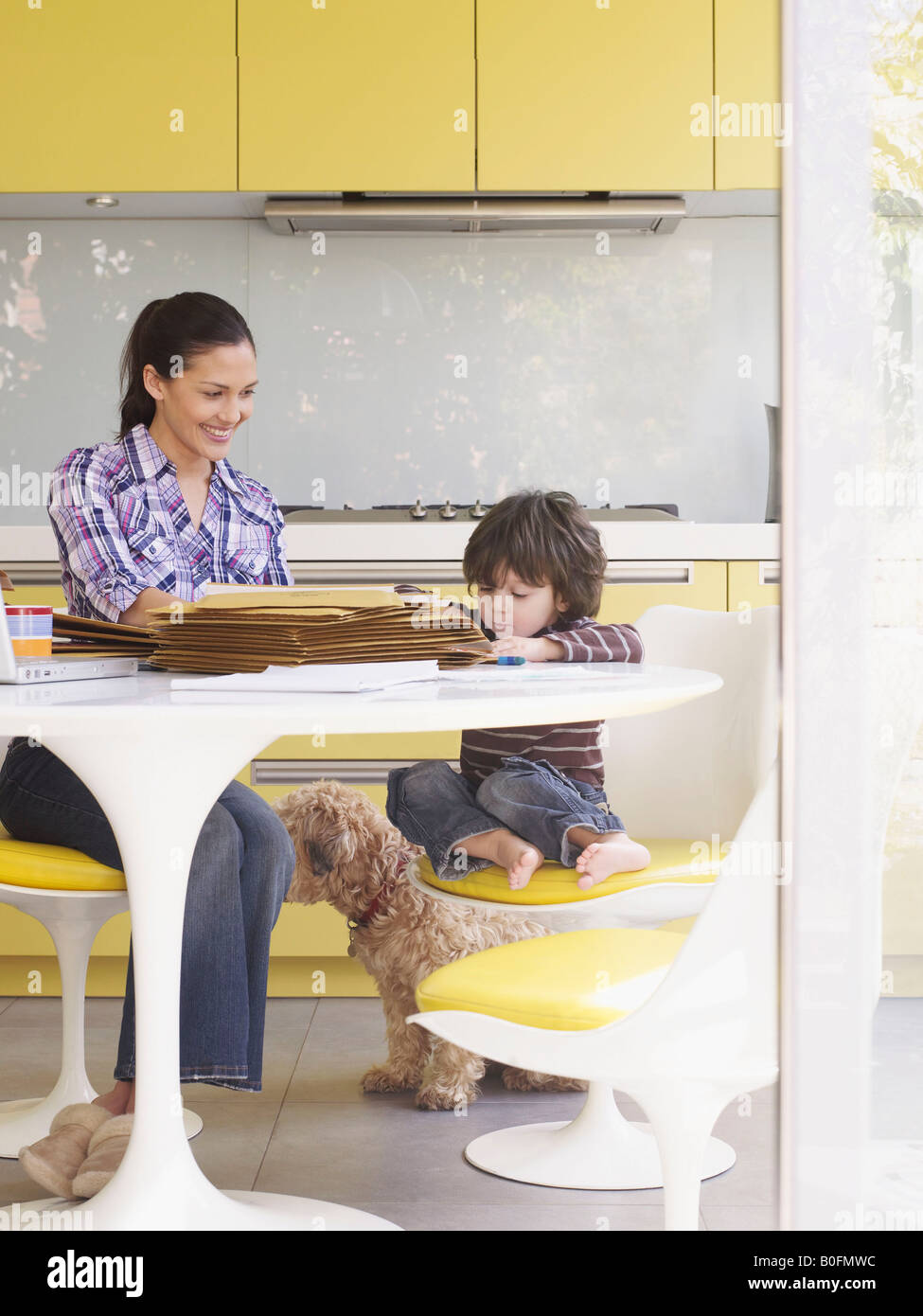 Woman working at home, with son at table - Stock Image