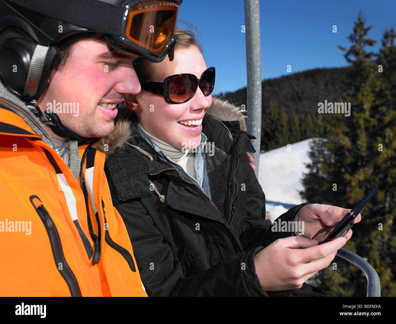 Couple playing game on ski-lift - Stock Image