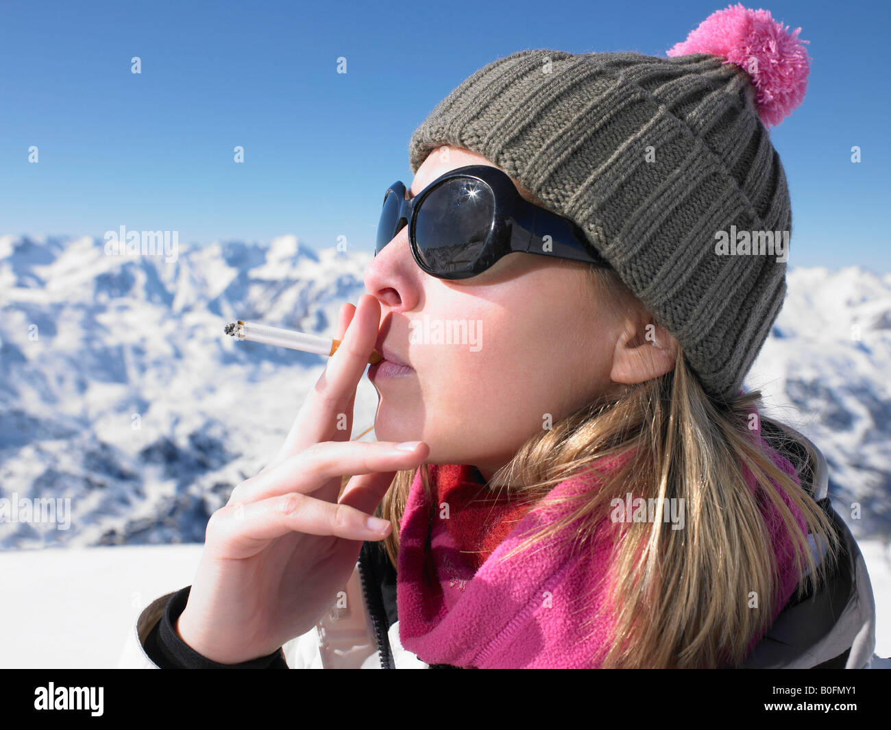 Young woman smoking in snow gear Stock Photo
