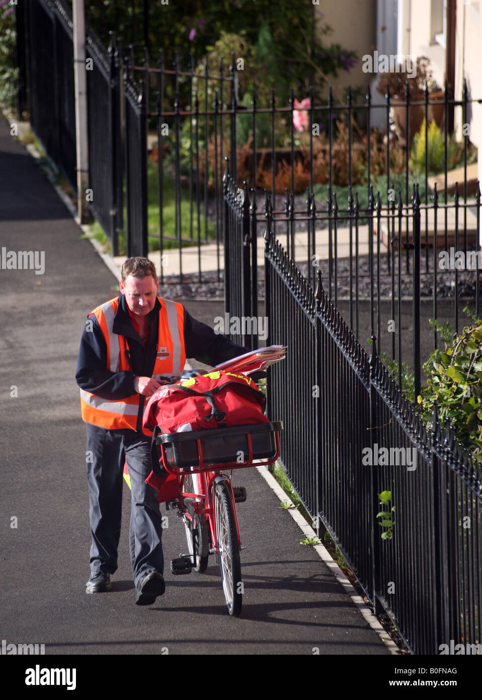 Postman with bike delivering letters in Haverhill Suffolk Stock Photo