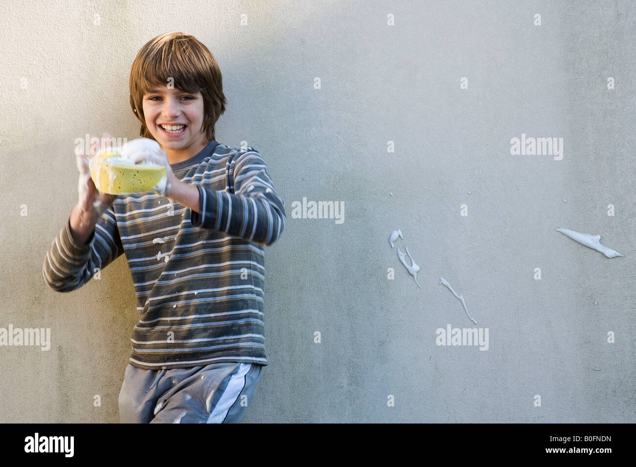 Boy playing with car sponge - Stock Image