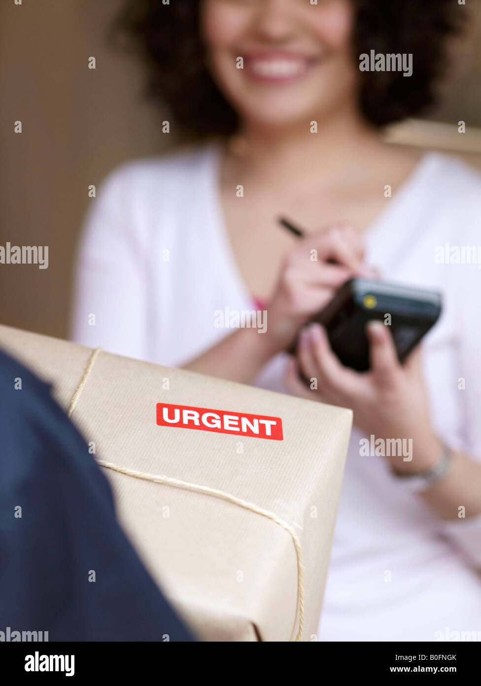 Woman signing for urgent delivery - Stock Image