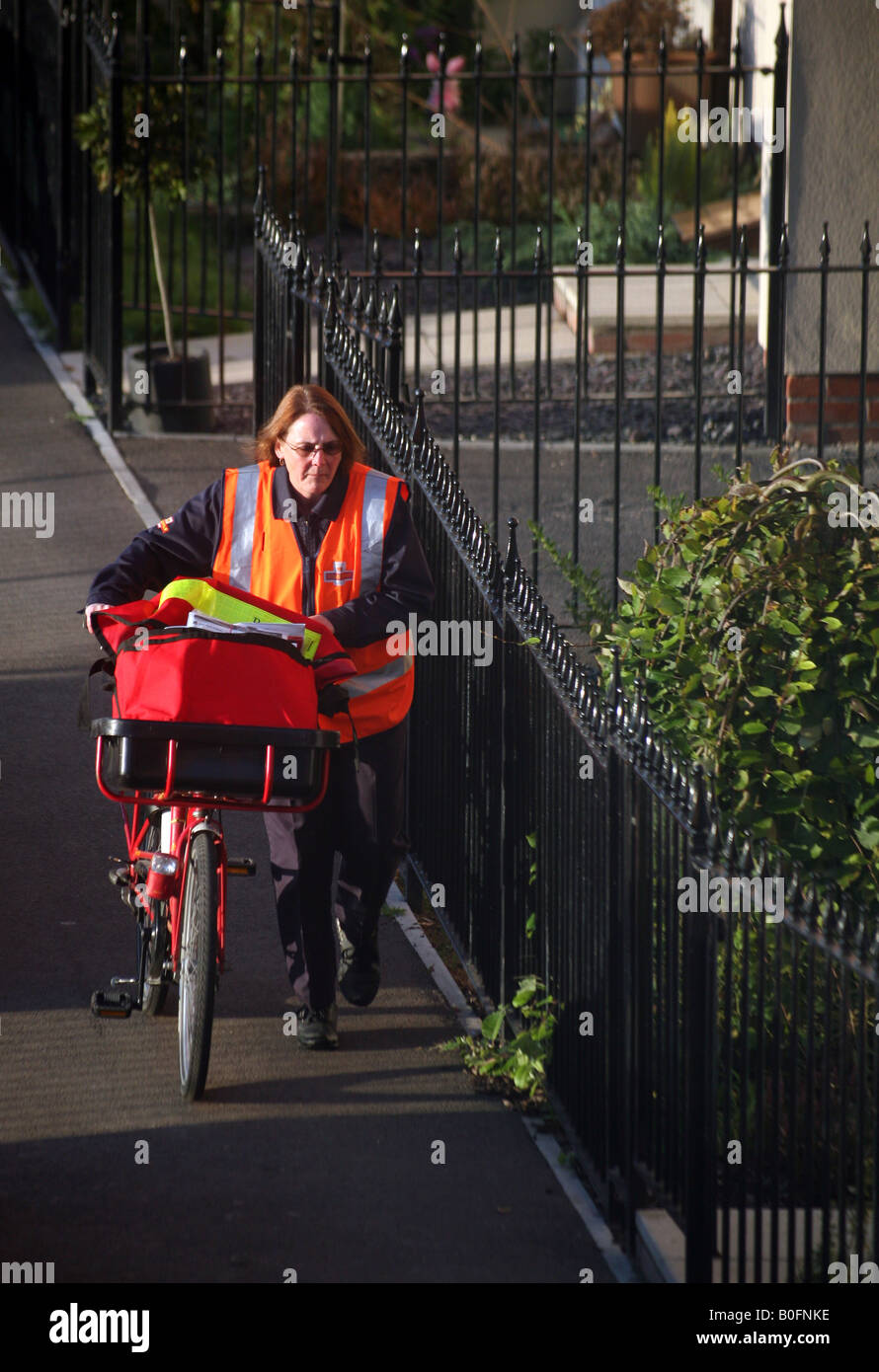 Postwoman with bike delivering letters in Haverhill Suffolk Stock Photo
