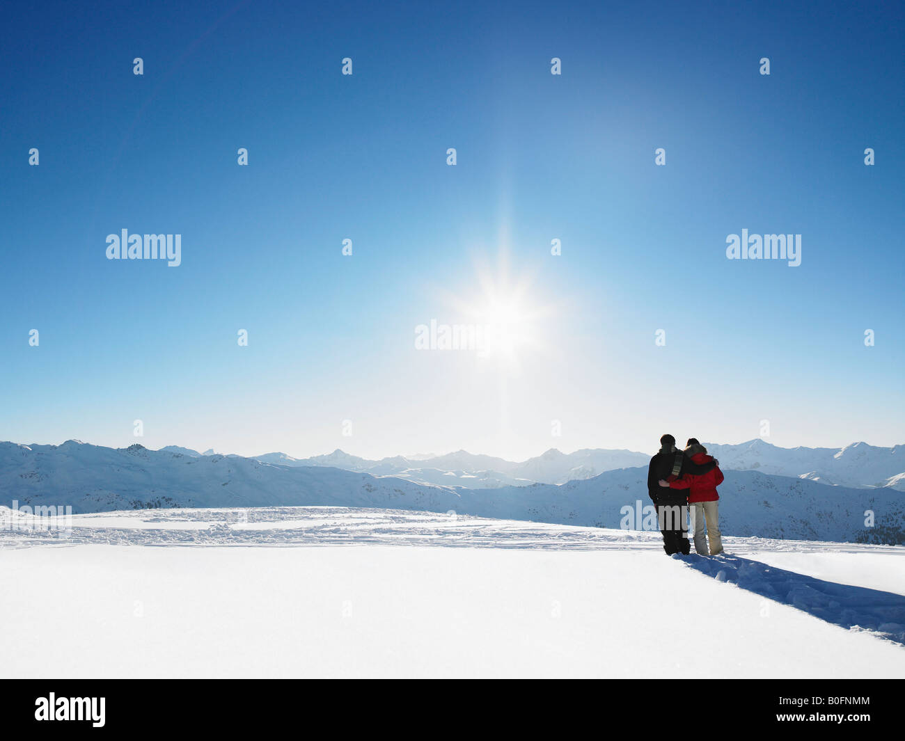 Couple walking in snow on mountain top - Stock Image