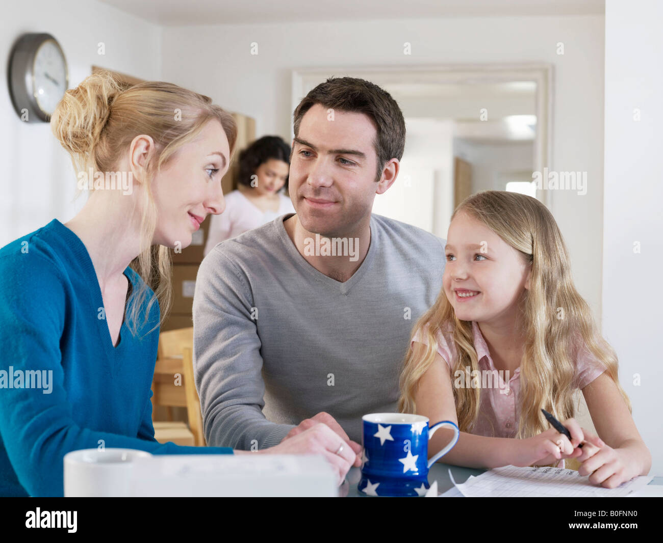 Family taking a break at kitchen table - Stock Image