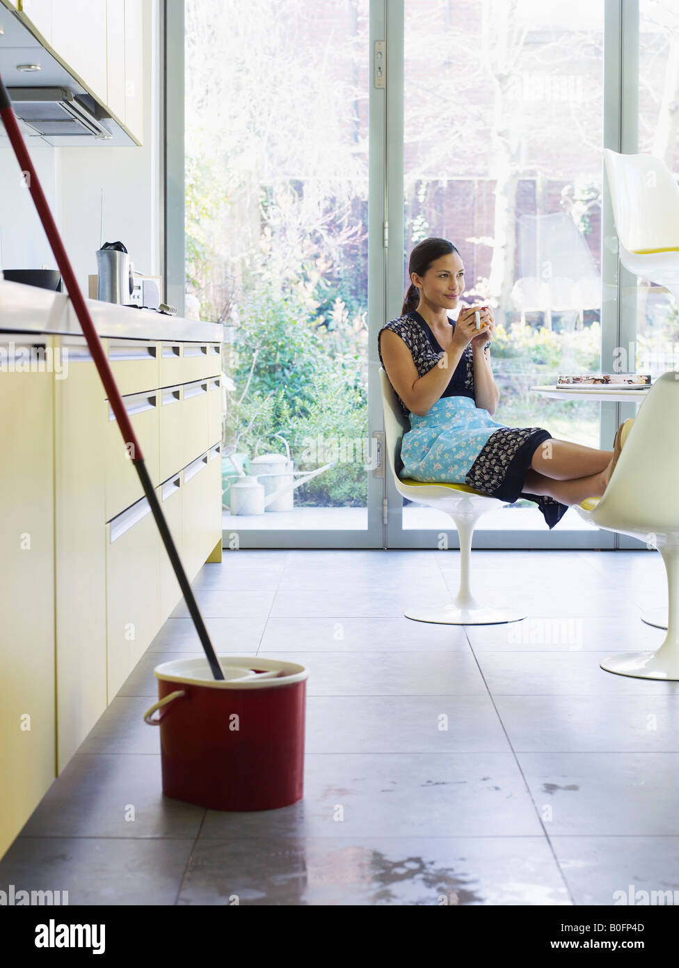Young woman relaxing, mop in foreground - Stock Image