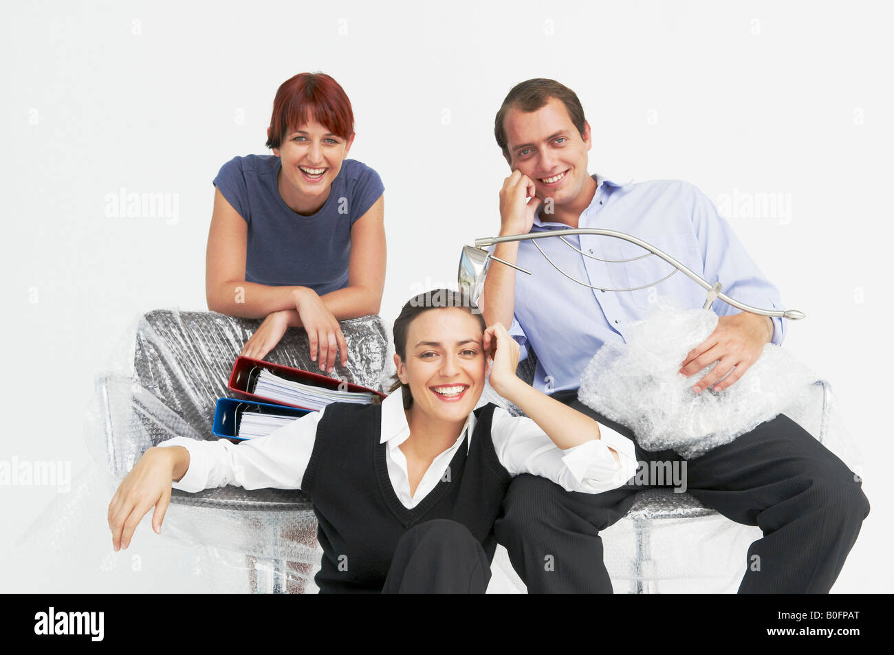 Three people moving into new office - Stock Image