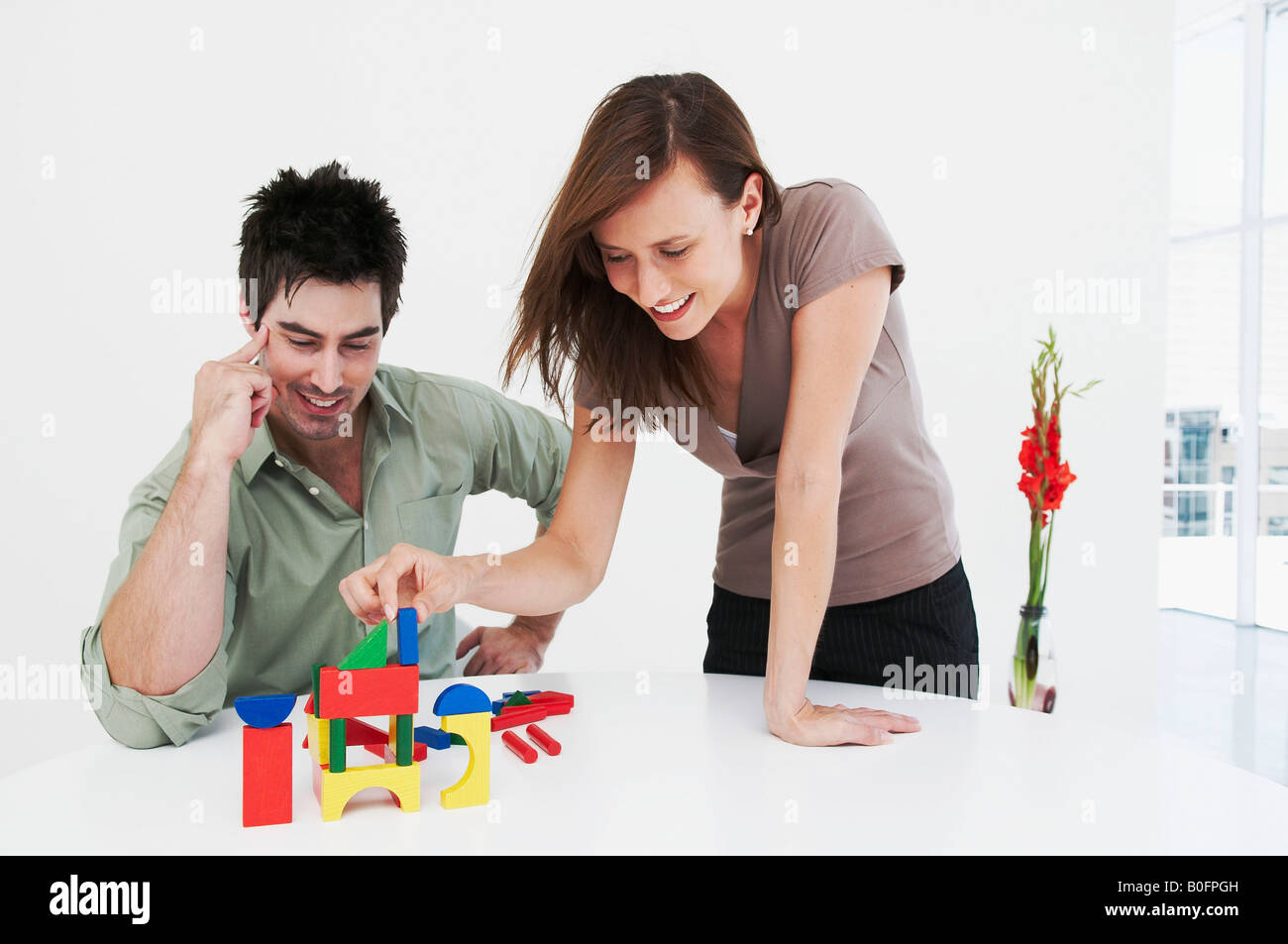 Man and woman happily build model house - Stock Image
