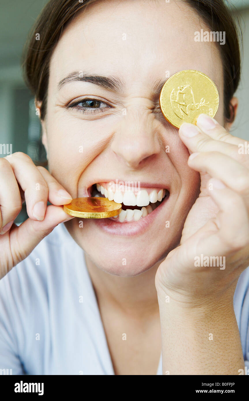 Amusing woman bites into gold coins - Stock Image