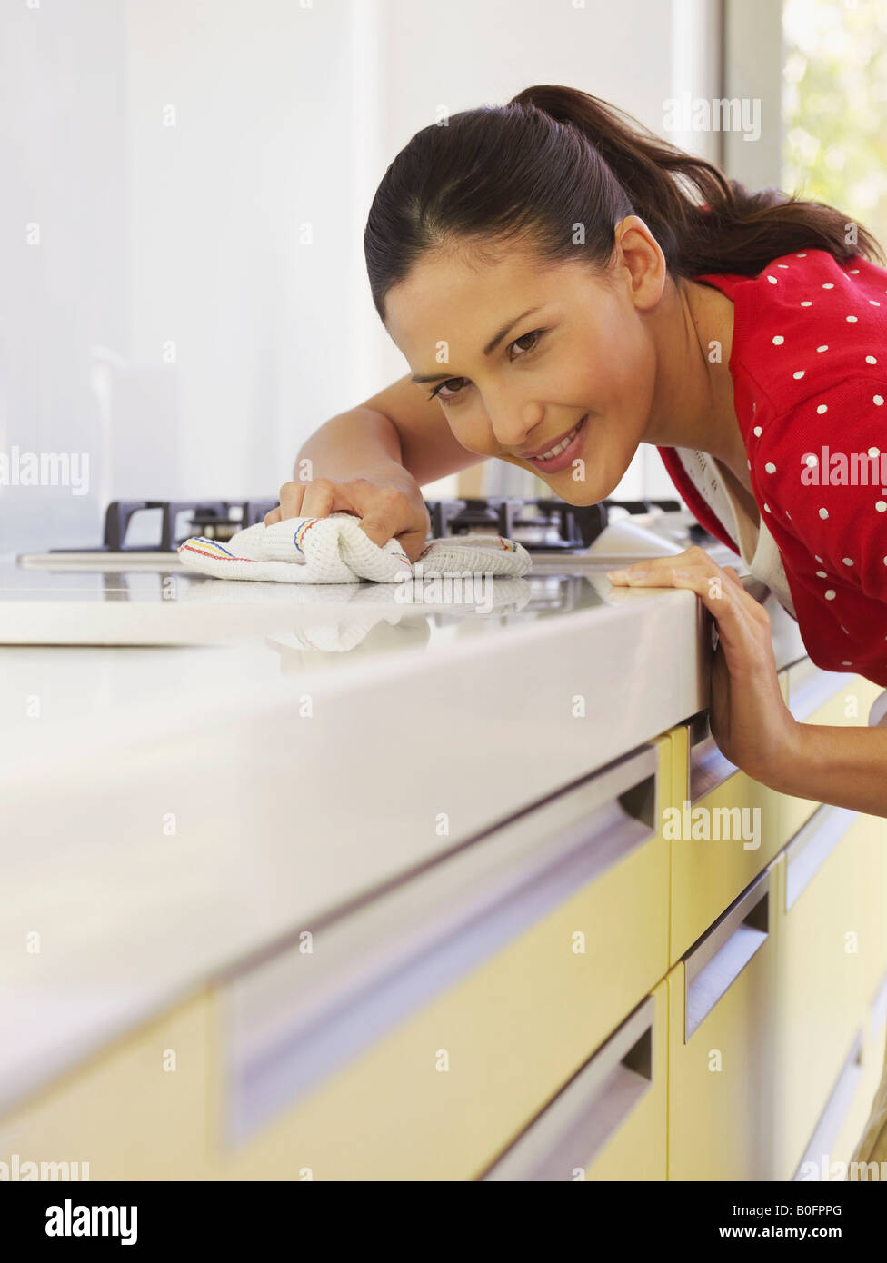 Young woman cleaning kitchen surface - Stock Image