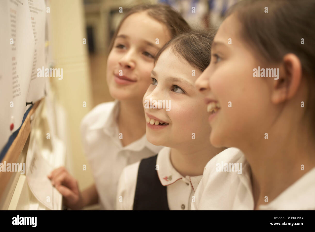 Girls reading message board - Stock Image
