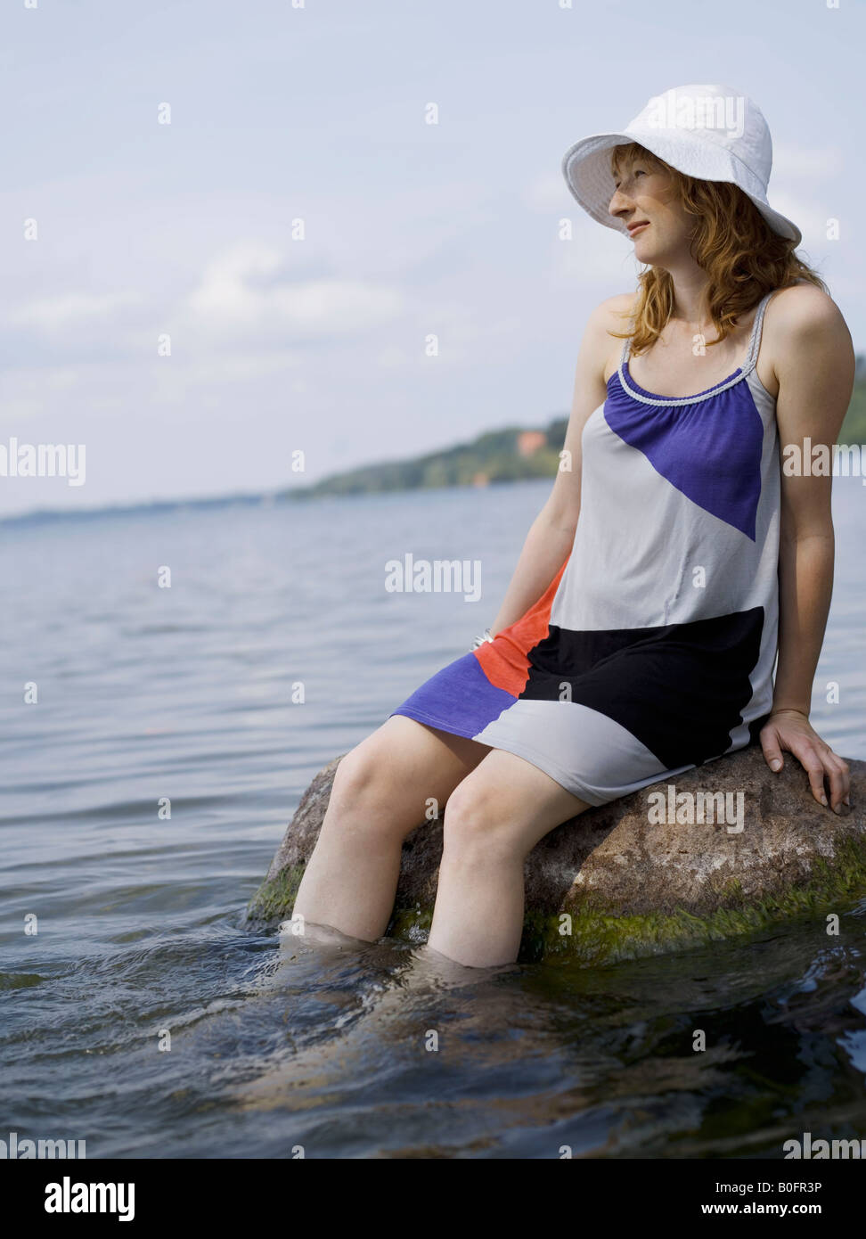 Woman sitting on rock in water - Stock Image