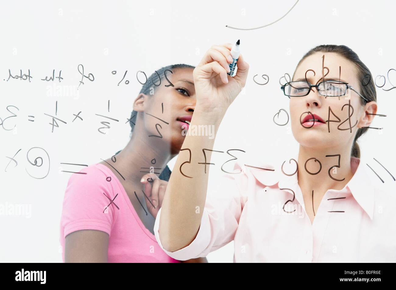Two women write on glass panel - Stock Image