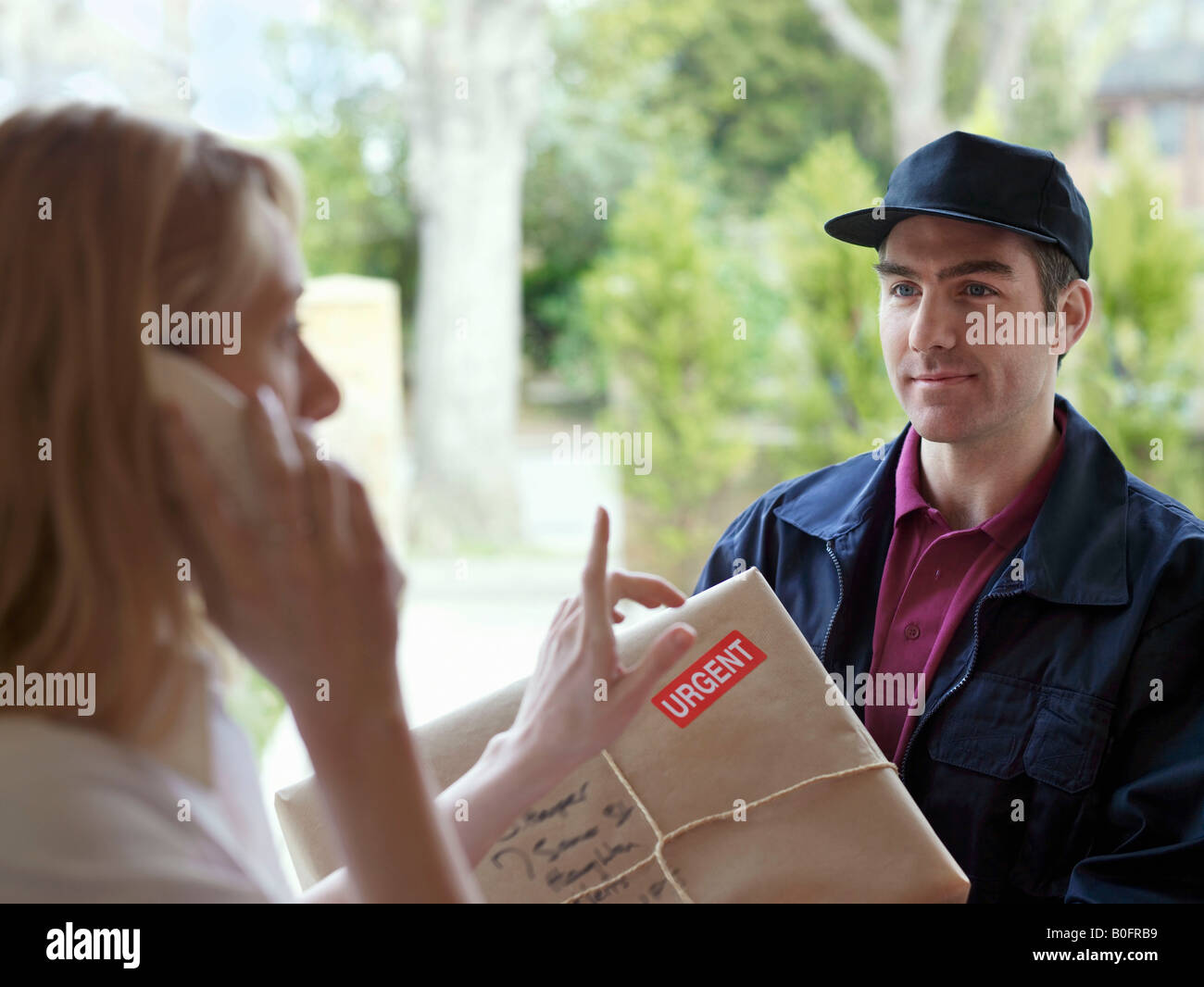 Woman on phone, courier in doorway - Stock Image
