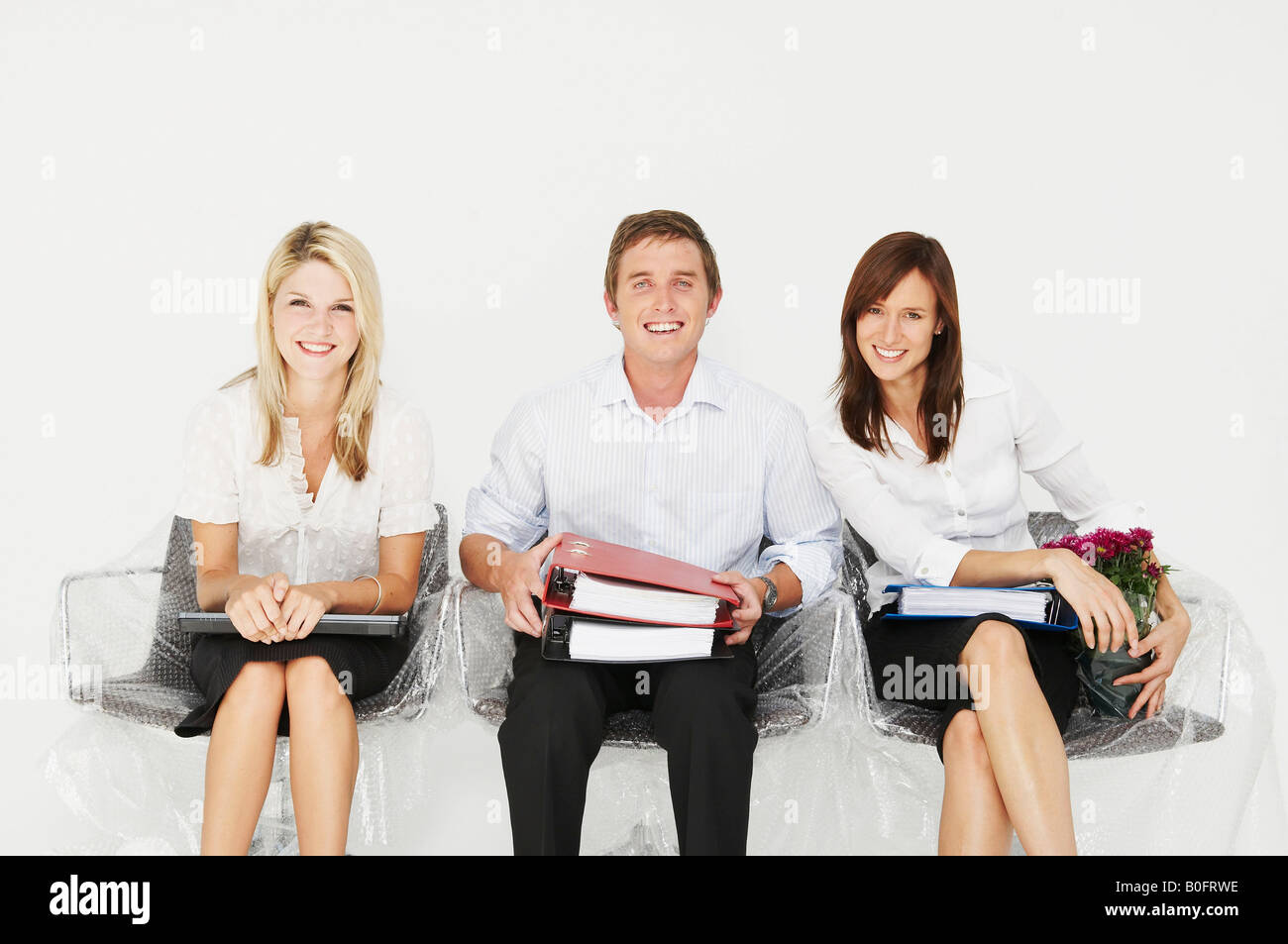 Three people smiling in new office - Stock Image
