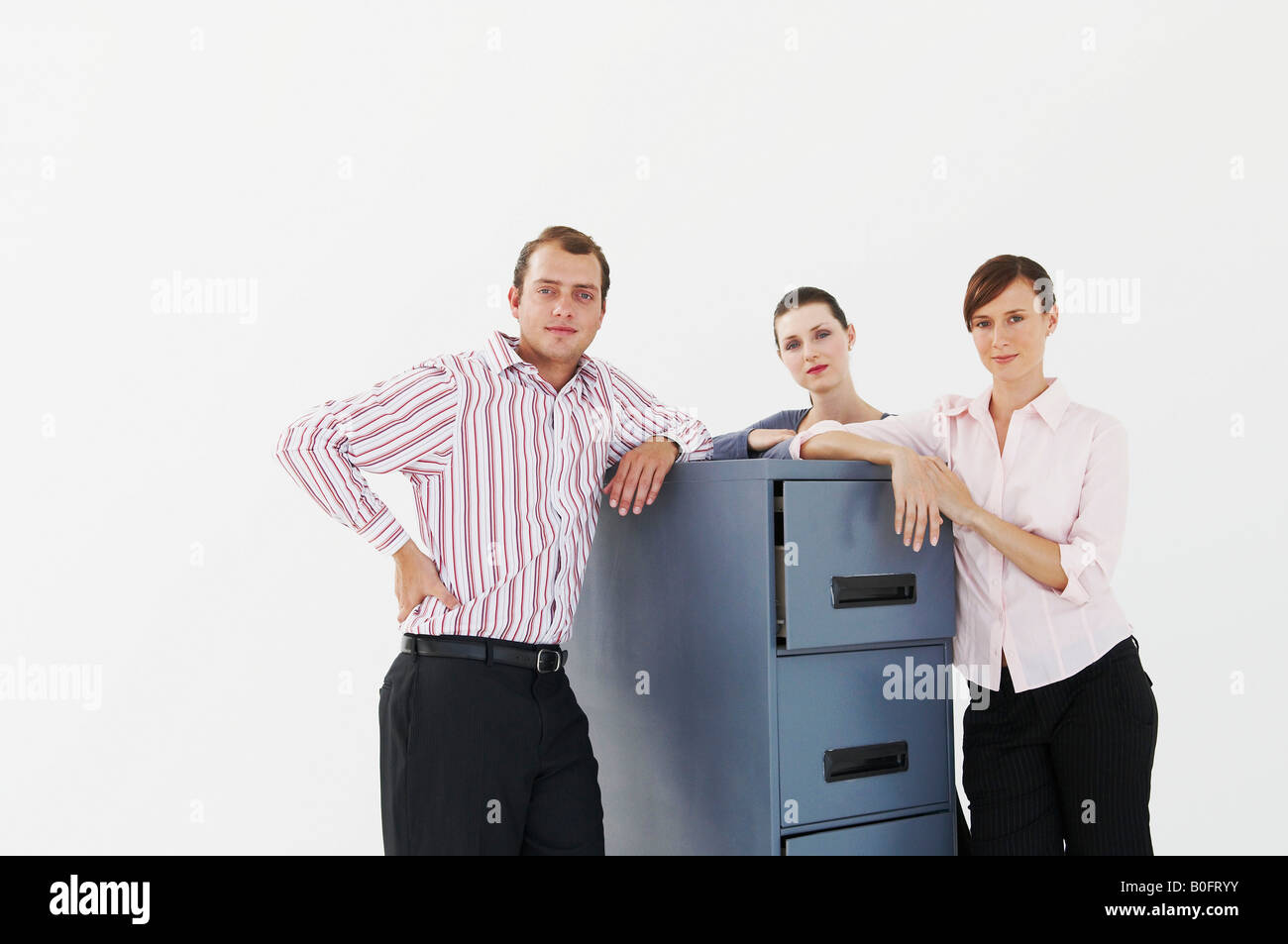 Three business people lean on cabinet - Stock Image