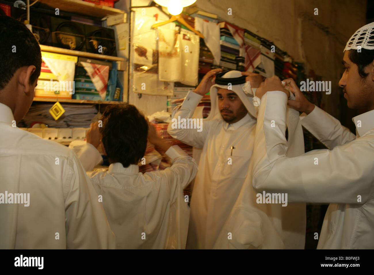 Men trying on traditional headdress at the Souq Waqif market in Doha, Qatar. Stock Photo