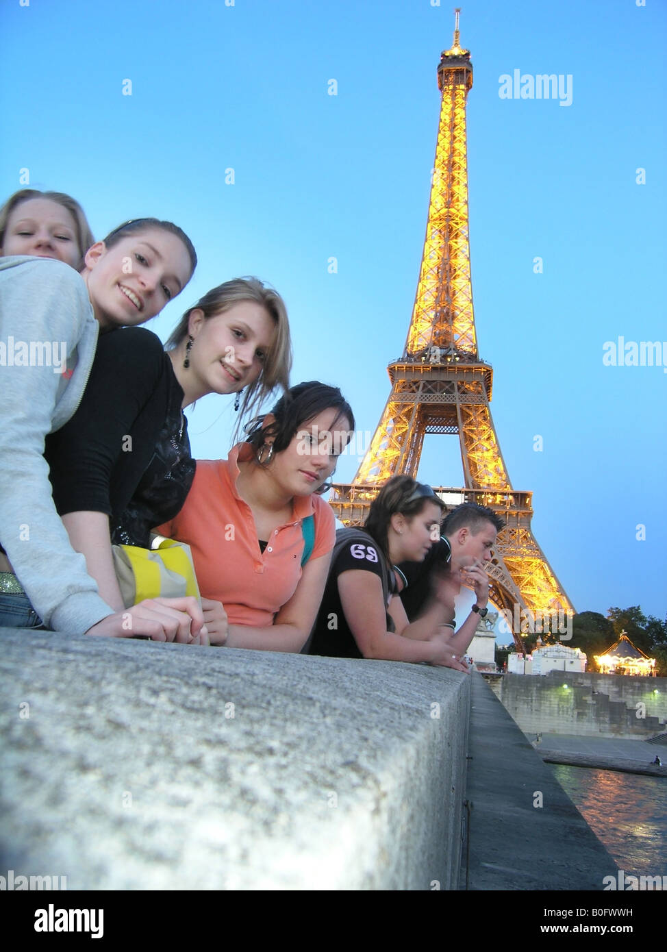 Six students posing on Pont D'iena with Eiffel Tower behind them at dusk Paris France - Stock Image