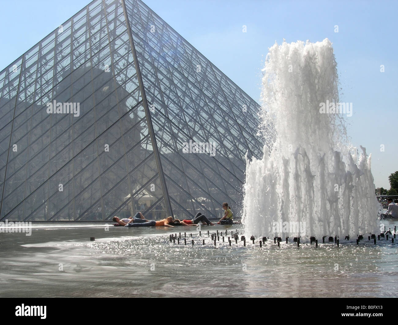 Detail view of Louvre Pyramid with fountain and relaxing tourists in the background Paris France Stock Photo