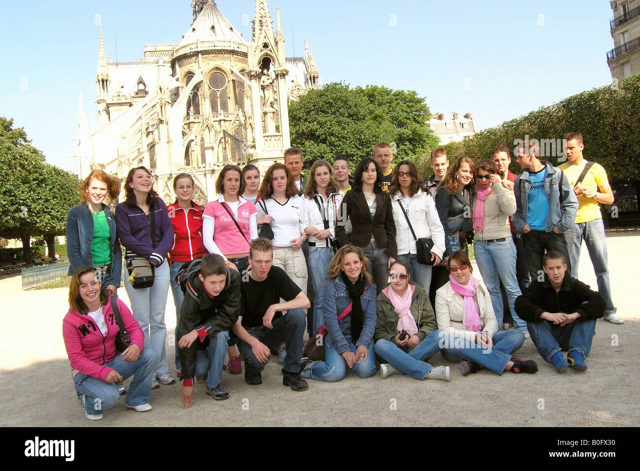 School group of Caucasian teenagers posing for camera in front of Notre Dame Paris France - Stock Image
