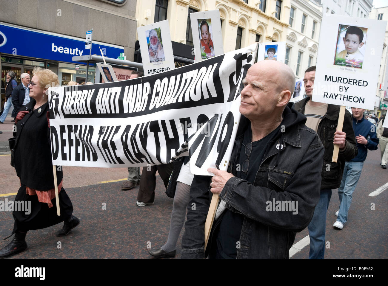 Eamonn McCann holds a banner saying 'Derry Anti War Coalition: Defend the Raytheon 9' demonstration through - Stock Image